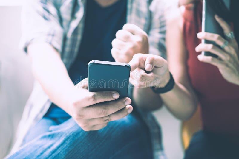 Agrupe os amigos que sentam e que usam o smartphone para a tecnologia da conexão e comece acima o projeto imagem de stock royalty free
