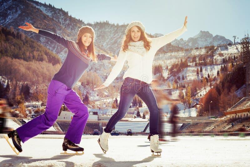 Agrupe a patinagem no gelo engraçada das meninas dos adolescentes exterior na pista de gelo foto de stock