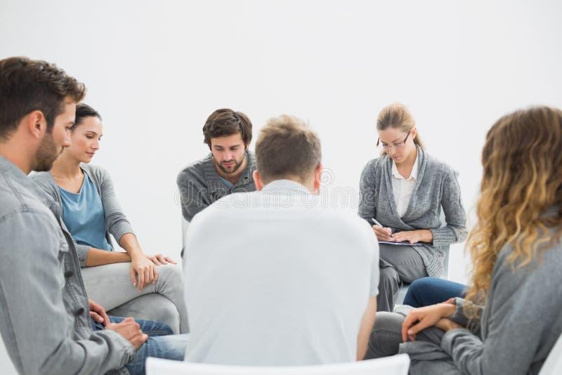 Agrupe a terapia na sessão que senta-se em um círculo fotos de stock