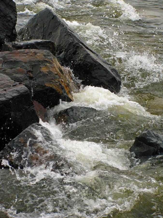 Agua áspera contra rocas oscuras imágenes de archivo libres de regalías