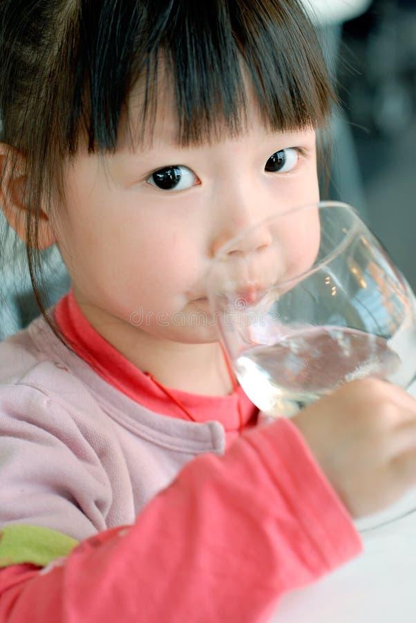Agua asiática linda de la bebida del niño imagen de archivo