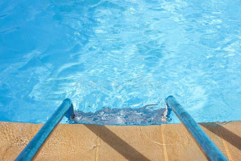 Agua azul clara y una escalera en la piscina fotos de archivo libres de regalías