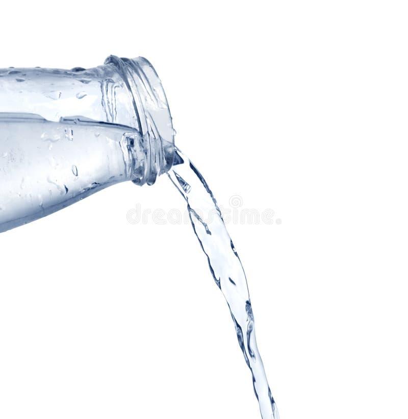 Agua azul que vierte de la botella en el vidrio fotografía de archivo