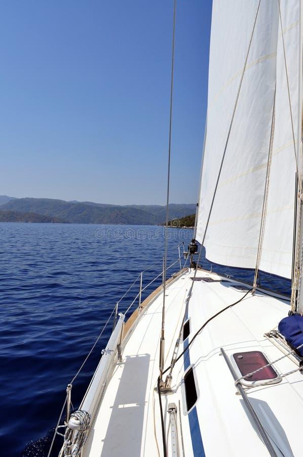 Agua azul ultramarina y tierra vistas de la cubierta del yate imagenes de archivo