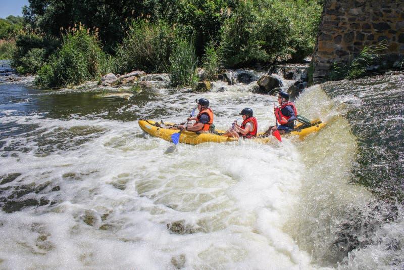 Agua blanca de tres hombres kayaking en el deporte del río, del extremo y de la diversión en la atracción turística fotografía de archivo libre de regalías