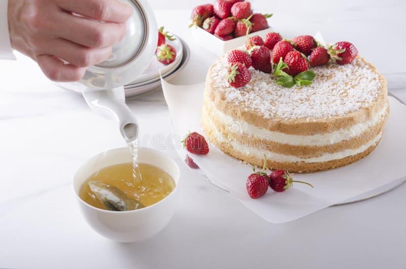 Agua caliente del pourig del camarero sobre la bolsita de t? Tiempo del té, torta de esponja deliciosa con crema y frutas foto de archivo