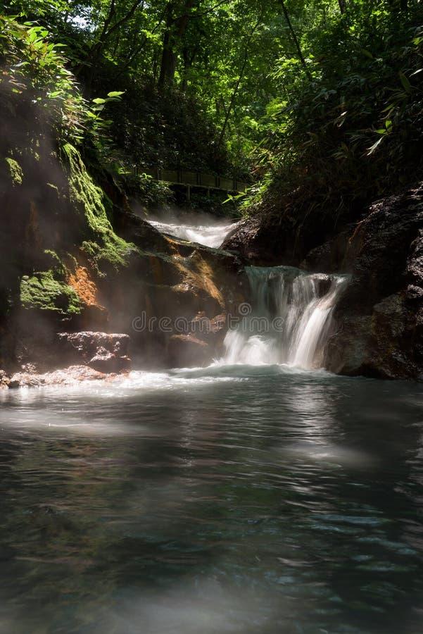 Agua caliente del río de Oyunumagawa que fluye de la charca de Oyunuma a través del valle Jigokudani del infierno imagenes de archivo