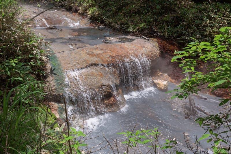 Agua caliente del río de Oyunumagawa que fluye de la charca de Oyunuma a través del valle Jigokudani del infierno fotos de archivo libres de regalías