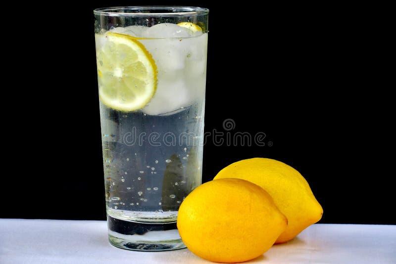 Agua chispeante con el limón en un vidrio transparente en un fondo negro imagenes de archivo