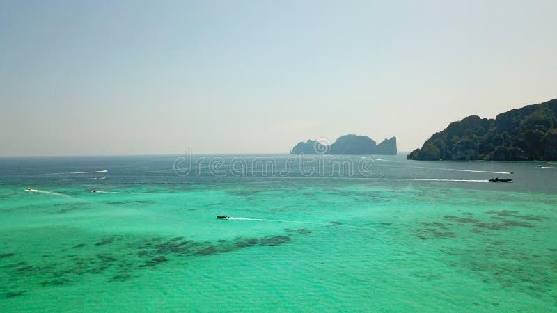 Agua clara azul con los barcos La isla tropical verde Phi Phi, palmeras crece foto de archivo libre de regalías