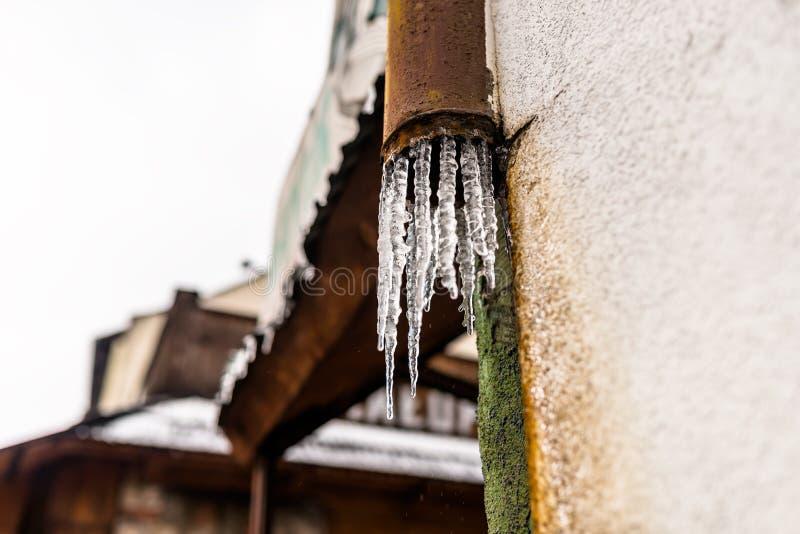 Agua congelada que fluye del tejado con haber dañado, oxidado, canal del metal que está en la fachada del edificio imagen de archivo