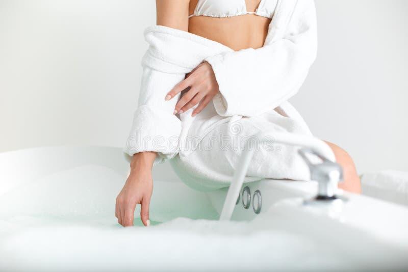 Agua conmovedora de la mujer joven en baño imagen de archivo