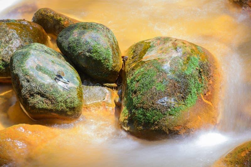 Agua corriente alrededor de rocas de oro fotos de archivo
