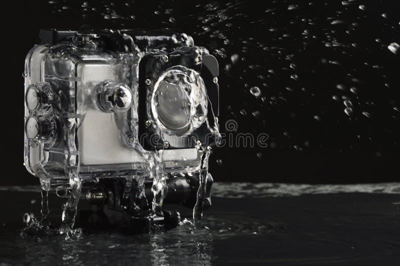 Agua corriente en la cámara impermeable de la acción en fondo de piedra negro mojado fotografía de archivo