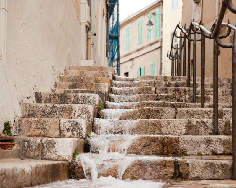 Agua corriente en los pasos en el viejo cuarto de Marsella fotos de archivo