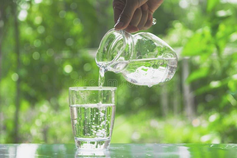 Agua de colada de la mano femenina de la jarra al vidrio fotografía de archivo