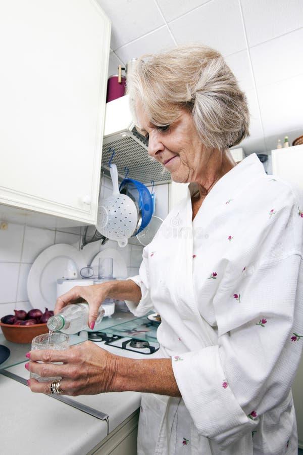 Agua de colada de la mujer mayor en vidrio mientras que se coloca en la encimera fotografía de archivo libre de regalías