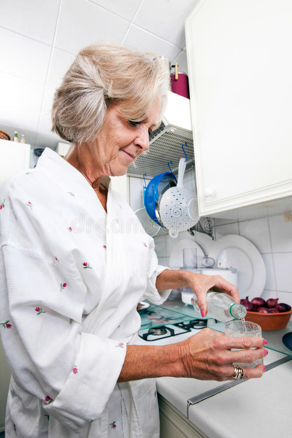 Agua de colada de la mujer mayor en vidrio mientras que se coloca en la encimera foto de archivo