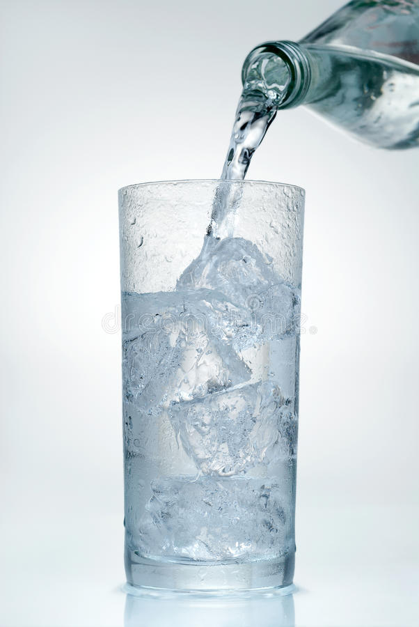 Agua de colada en un vidrio imagen de archivo