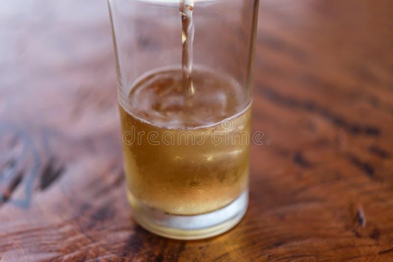 Agua de colada de la cerveza adentro al vidrio con hielo y espuma fotografía de archivo libre de regalías
