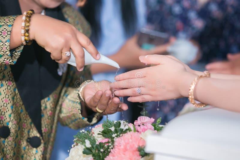 Agua de colada de la huésped con las manos de novia y del novio en relanzamiento del agua fotografía de archivo