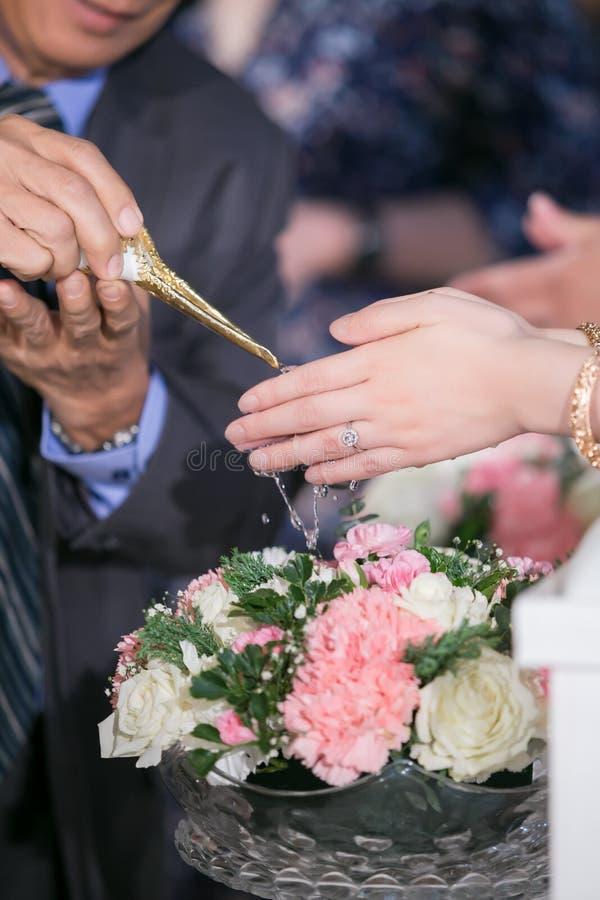 Agua de colada de la huésped con las manos de novia y del novio en relanzamiento del agua imagen de archivo