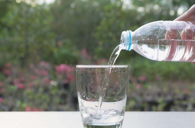 Agua de colada de la mano femenina de la botella al vidrio en la naturaleza fotografía de archivo