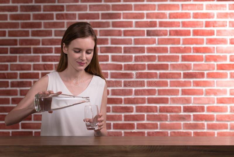 Agua de colada de la mujer joven de la botella en el vidrio en el cuarto foto de archivo libre de regalías
