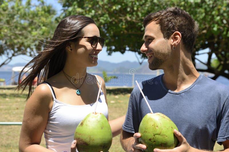 Agua de consumición del coco de los pares felices imagenes de archivo