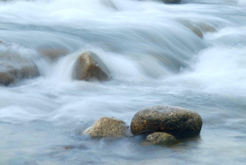 Agua de la corriente que fluye más allá de piedras fotos de archivo libres de regalías