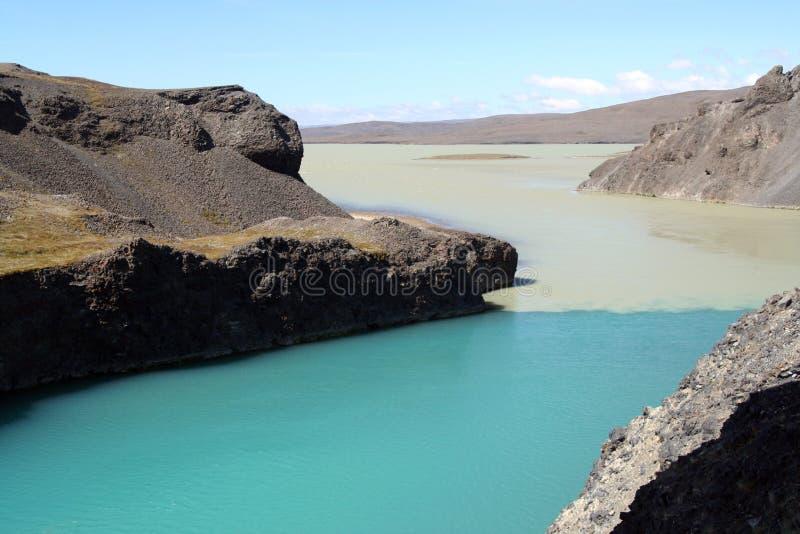 Agua de la turquesa que fluye en el pequeño barranco de las colinas negras de la lava - lago Hálslón en Islandia imágenes de archivo libres de regalías