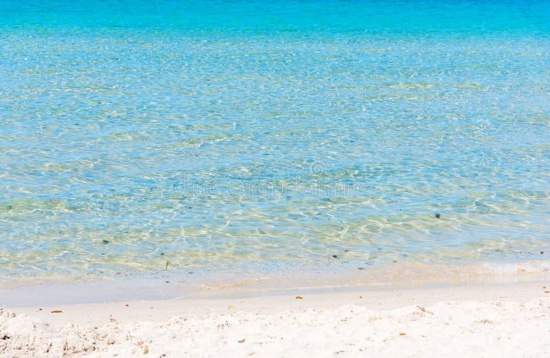 Agua de la turquesa y arena blanca en Alghero imagenes de archivo