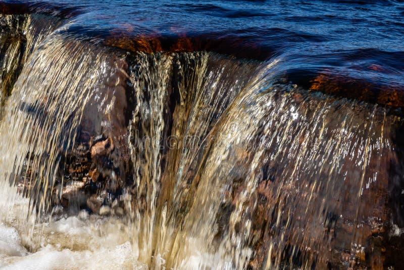 Agua de manatial coloreada de oro que limpia con un chorro de agua sobre una presa inundada fotografía de archivo