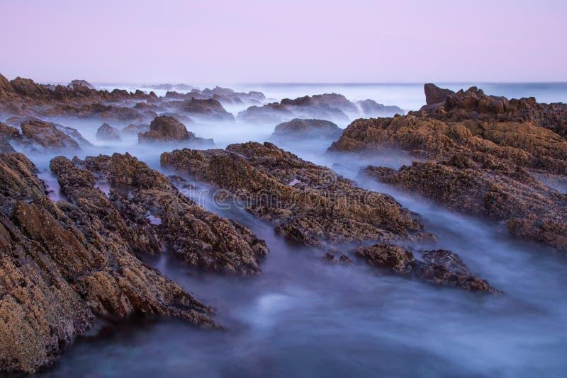 Agua de mar lechosa sobre rocas en la costa foto de archivo libre de regalías