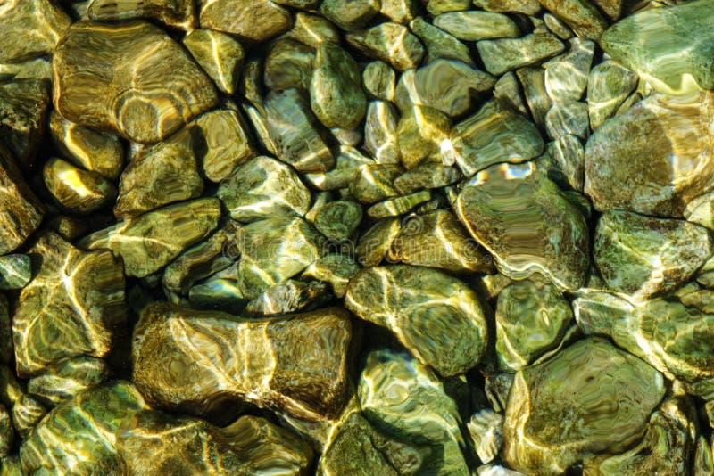 Agua de mar transparente clara a través de la cual usted puede ver la textura del fondo de las piedras Subacuático imágenes de archivo libres de regalías