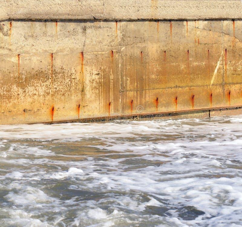Agua de mar y el muro de cemento viejo imagenes de archivo