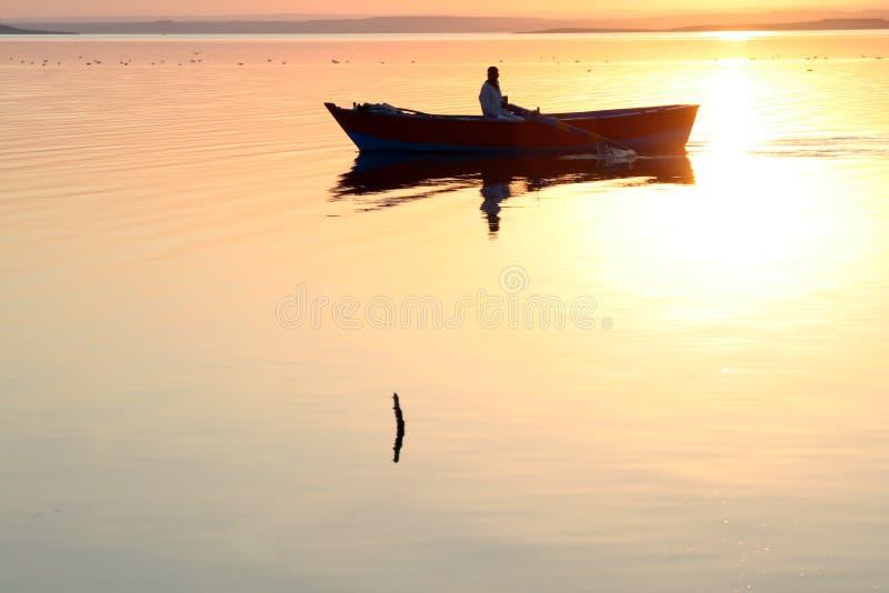 Agua de oro de la silueta del barco fotografía de archivo