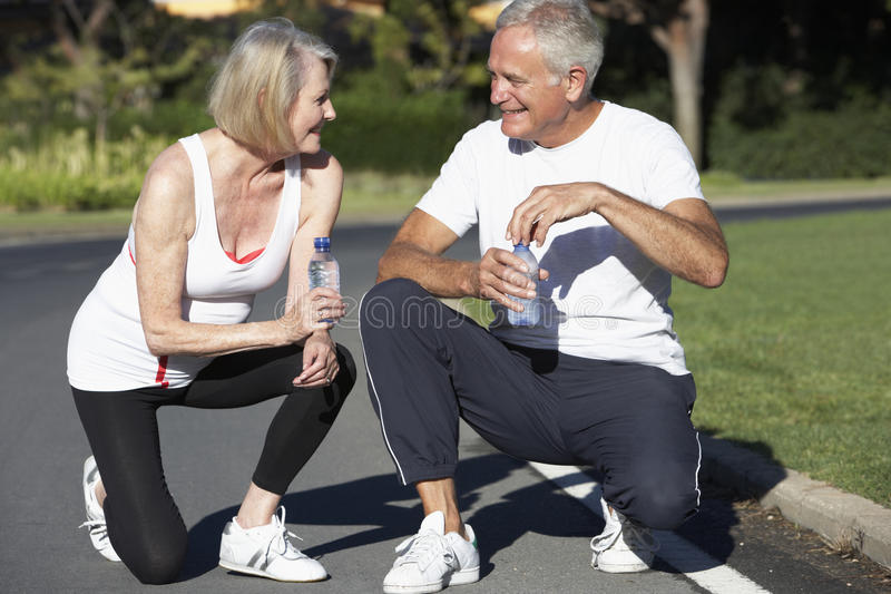 Agua de reclinación y potable de los pares mayores después del ejercicio imagen de archivo libre de regalías