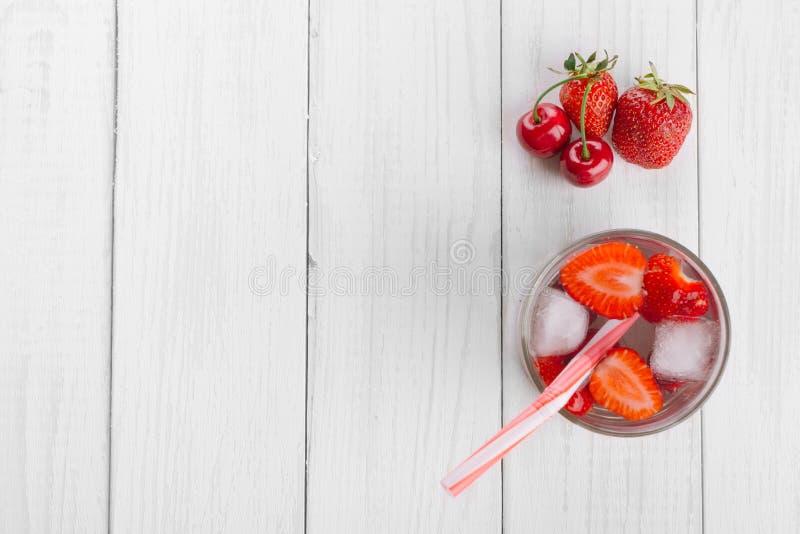 Agua de restauración de bayas rojas en un vidrio en la tabla de madera Bebidas sabrosas y sanas hechas en casa fotografía de archivo