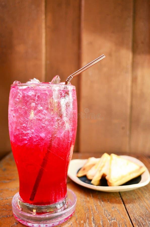 Agua de soda roja con el bocadillo fotografía de archivo