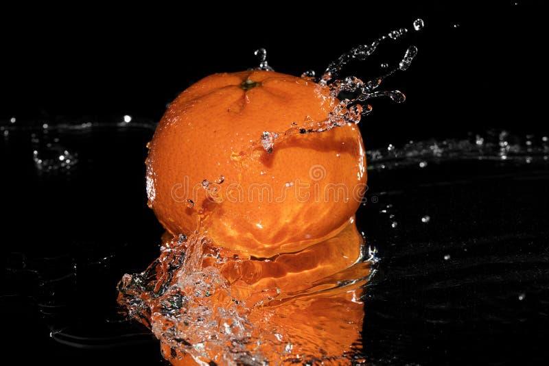 Agua del chapoteo de la mandarina en el espejo negro del fondo fotos de archivo