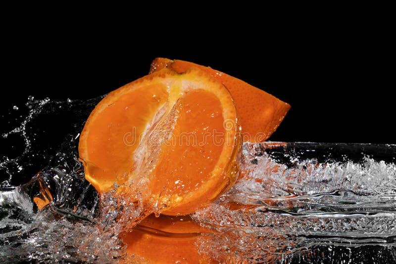 Agua del chapoteo de la mandarina en fondo negro del espejo fotos de archivo