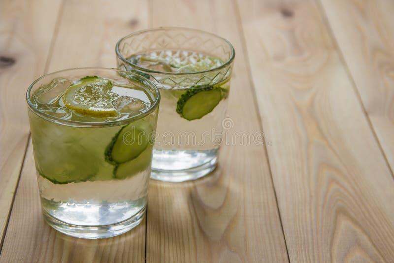 Agua del Detox con el pepino y el limón en la tabla de madera Pepino le foto de archivo libre de regalías