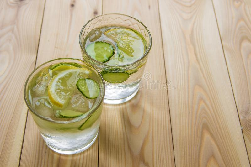 Agua del Detox con el pepino y el limón en la tabla de madera Pepino le imagen de archivo