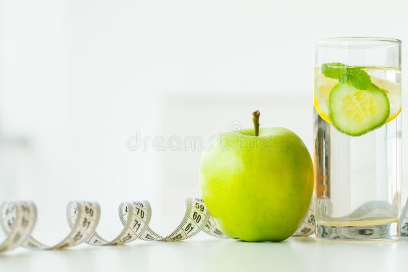 Agua del manzana, de cristal con las hojas de menta, limón y pepino verdes, fotografía de archivo libre de regalías