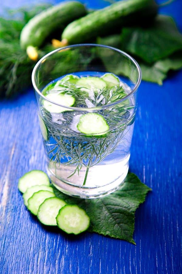 Agua del pepino en vidrio con eneldo en fondo de madera azul Detox, dieta fotos de archivo libres de regalías