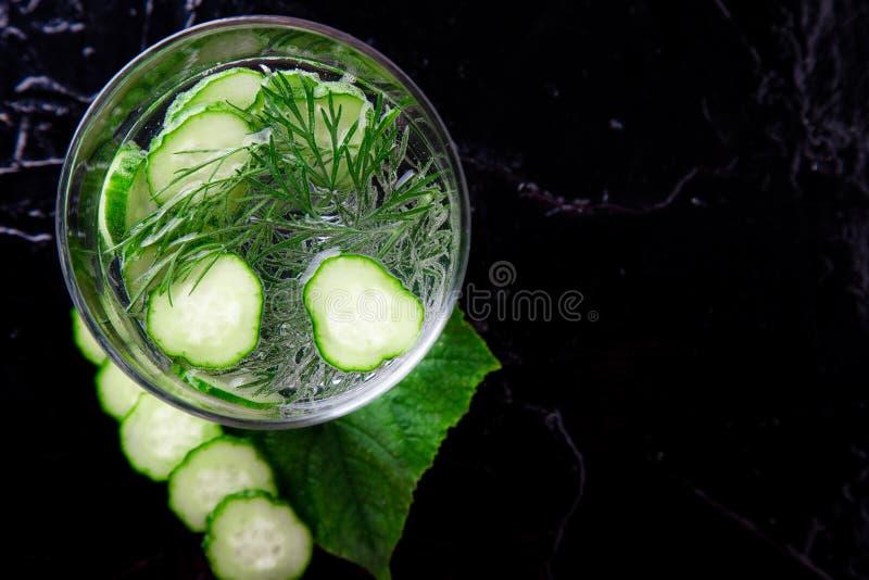 Agua del pepino en vidrio con eneldo en fondo negro Detox, dieta Contraluz Visión superior Copie el espacio imagen de archivo libre de regalías