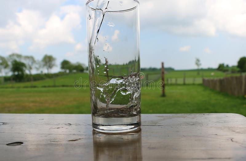 Agua dulce que cae en un vidrio imagenes de archivo