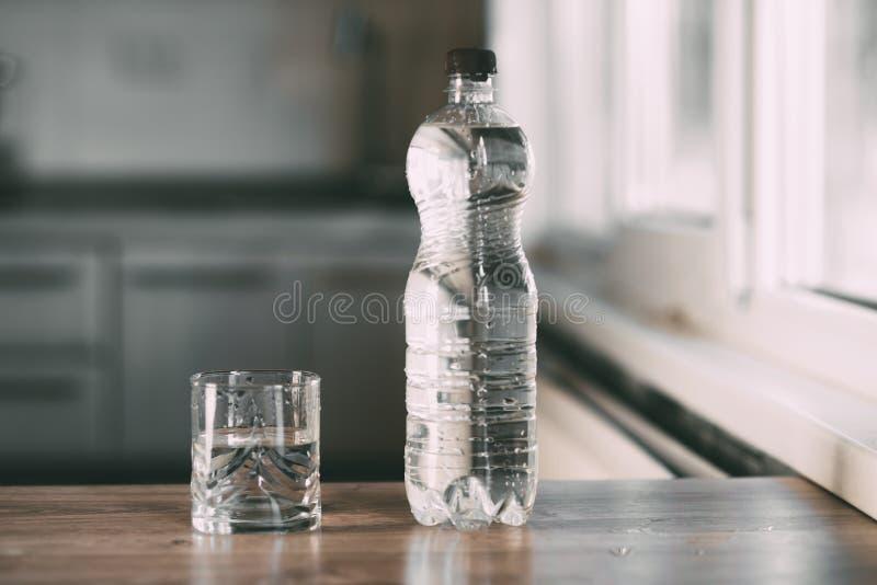 Agua en una botella y un vidrio en la tabla en casa en la cocina imagenes de archivo