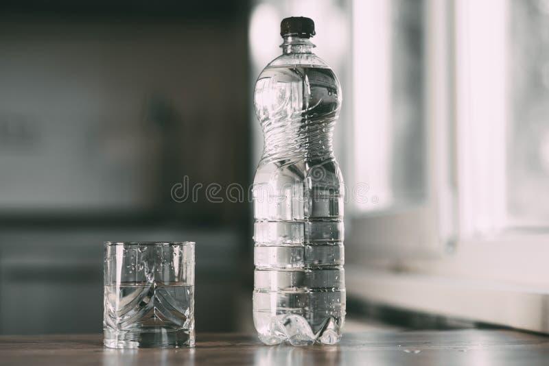 Agua en una botella y un vidrio en la tabla en casa en la cocina foto de archivo